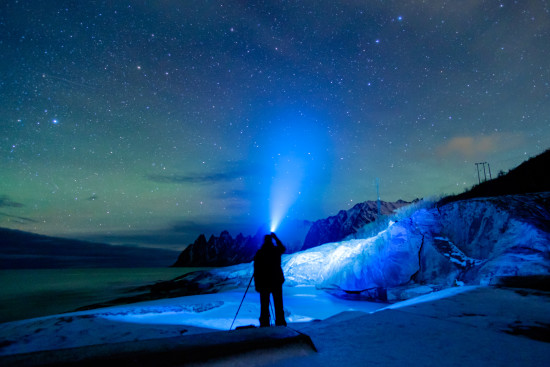 Photographer with headlamp at night in front of starry sky in winter